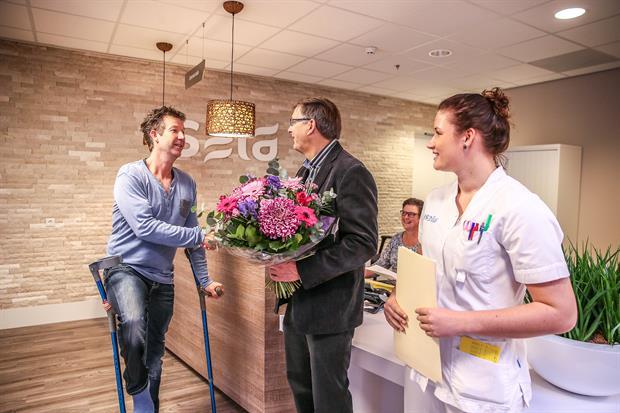 Fotobijschrift 1.  Daan Tolmeijer kwam voor een enkeloperatie en werd verwelkomd door leidinggevende Jan van Raan en verpleegkundige Shannon van Zelm.
