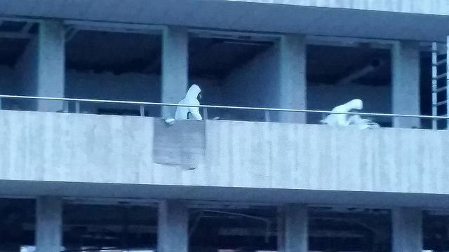 Photo of Mannen met witte pakken werken nog even door