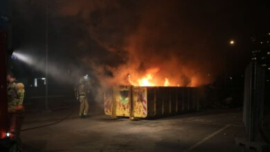 Photo of Brandweer blust brand in grote container met bouwafval