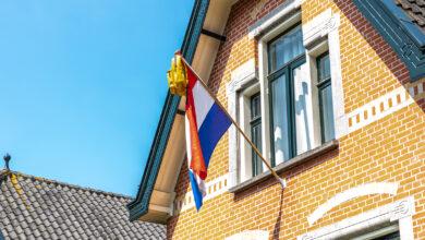 Photo of Examenleerlingen hangen feestelijk hun vlaggen en tassen uit